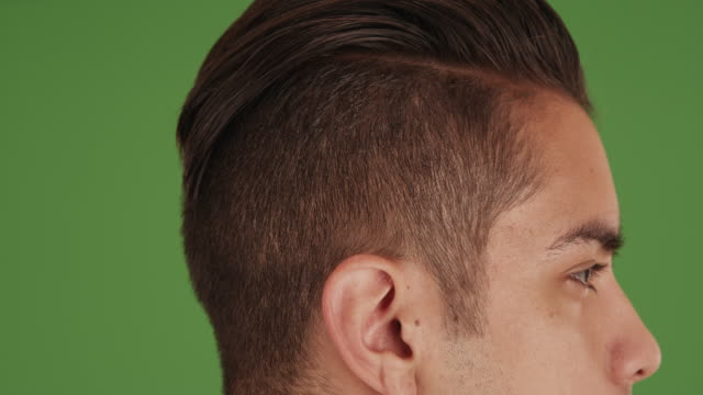 side view of young millennial man with undercut standing on green screen - standing stock videos & royalty-free footage