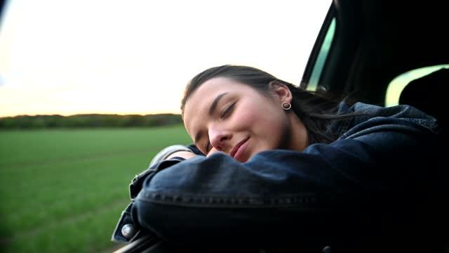 vídeos y material grabado en eventos de stock de side view of young woman leaning out from car window - actividad móvil general
