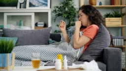 Side view of young woman taking temperature with thermometer in house on sofa