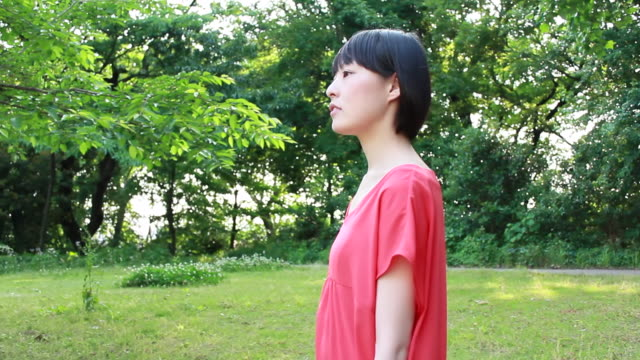 MS TS Side View of young woman walking in park / Nakano, Tokyo, Japan