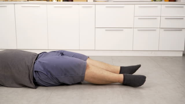 side view: overweight man's leg exercising and doing sit-ups in his kitchen - sit ups stock videos & royalty-free footage