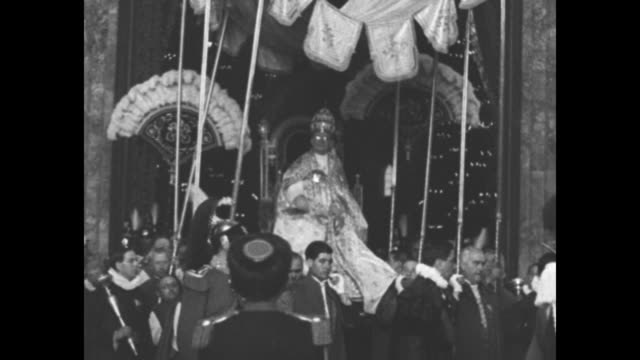 Side view Pope Pius XI sitting on portable throne being carried above entourage can see poles of canopy / Pope being carried his entourage in costume...