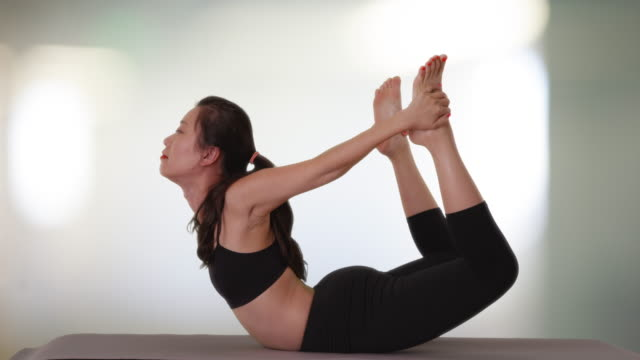 side view portrait of active young woman practicing yoga inside fitness center - 弓のポーズ点の映像素材/bロール
