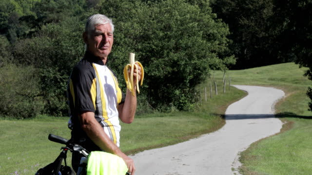 side view portrait of senior adult cycler eating a banana on countryside - only men stock videos & royalty-free footage