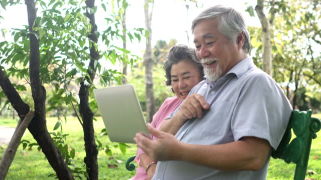 side view : senior asian couple are exciting to use notebook - southeast asian ethnicity stock videos & royalty-free footage