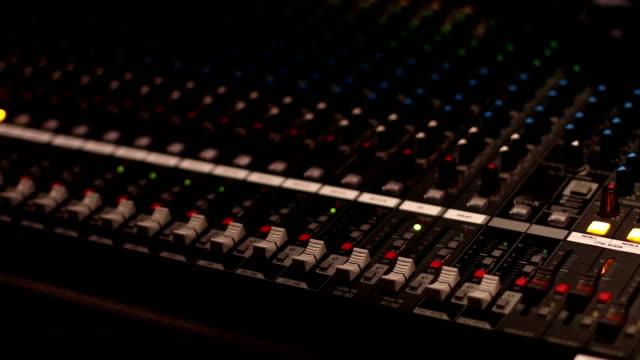 vidéos et rushes de coup de vue latérale d'un musicien travaillant sur la console de mixage audio dans un studio de musique - matériel hi fi