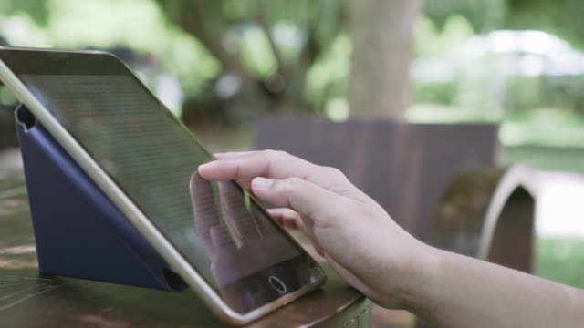 side view shot person turning e-book page on digital tablet - e reader stock videos & royalty-free footage