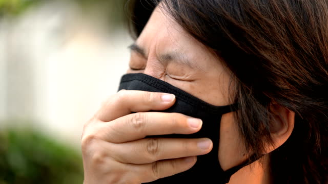 side view sick woman coughing under air pollution mask - pollution mask stock videos and b-roll footage