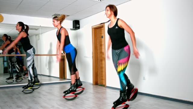 side view slow motion shot of three young women in the health club excersising jumping in kangoo jump shoes - sports training drill stock videos & royalty-free footage