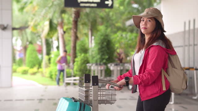 side view: solo beautiful asian woman, a traveler with long black hair, hat, shoulder bag, and luggage on pushcart waiting on airport terminal to looking taxi, transportation to explore the new journey. - shoulder bag stock videos & royalty-free footage