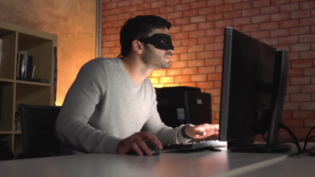 side view: unrecognizable computer hacker or spy with a black mask using computer pc late at night in a modern office, passing network security and privacy, searching and stealing e-mail, business, and intellectual property. - obscured face stock videos & royalty-free footage