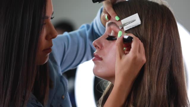 彼女の女性の顧客にマスカラを置くメイクアップアーティストのサイドビュービデオ - メイクアップアーティスト点の映像素材/bロール