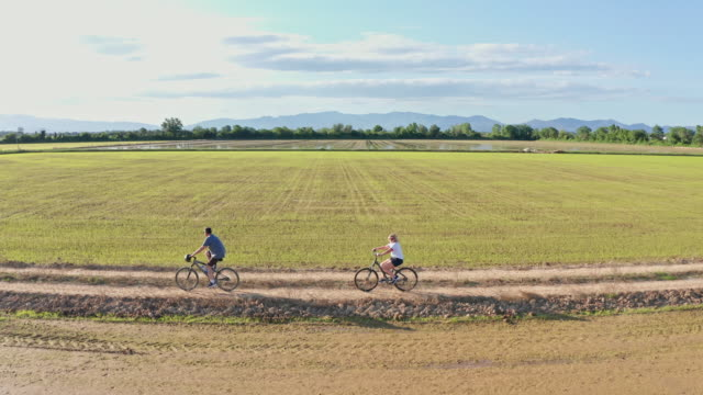 side view video of couple riding bikes in countryside - stabilimento sportivo video stock e b–roll