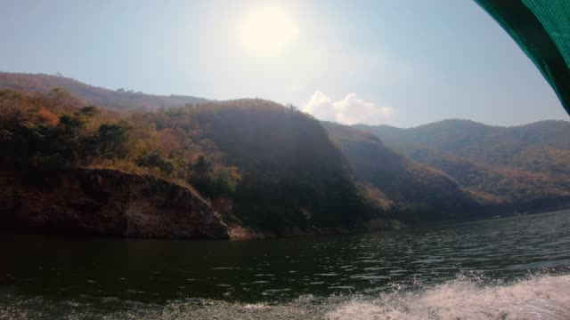 side view when boat driving in river in forest and mountain.summer travel
