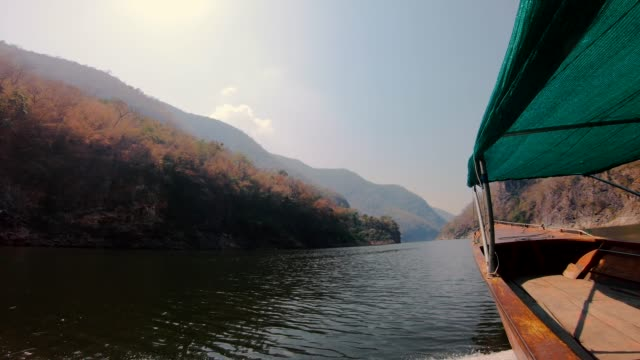 side view when boat running in river in forest and mountain.summer travel
