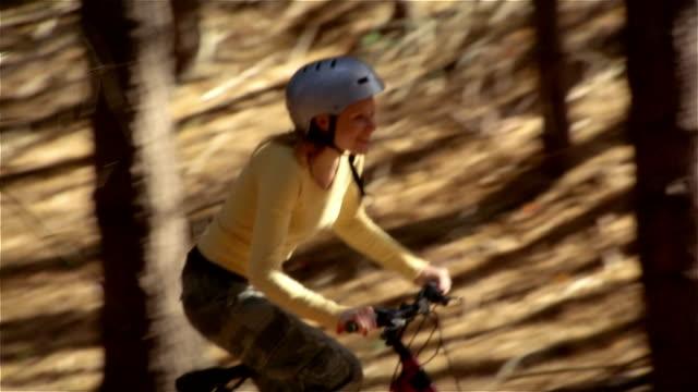 vídeos de stock, filmes e b-roll de side view woman riding mountain bike uphill in the woods - colina acima