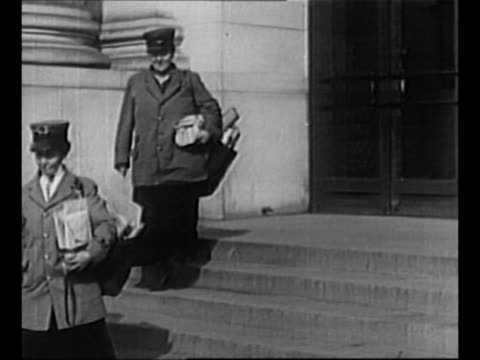 Side view woman stands on small platform outside building paints / two women exit building dressed as postal carriers and carrying bags of mail /...