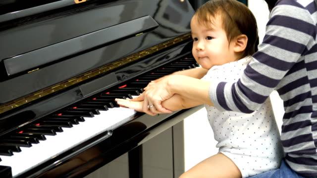 sidovy: unga mor lär sin son att spela piano men han betala uppmärksamhet på andra - människofinger bildbanksvideor och videomaterial från bakom kulisserna
