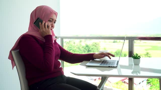 vidéos et rushes de vue latérale: jeunes femmes d'affaires musulmanes en tissu religieux en hiver à l'aide d'un smartphone, ordinateur portable pour travailler pendant le travail hors du bureau sur le balcon d'un hôtel, appartement parmi la scène verte, vue non ur - non urban scene
