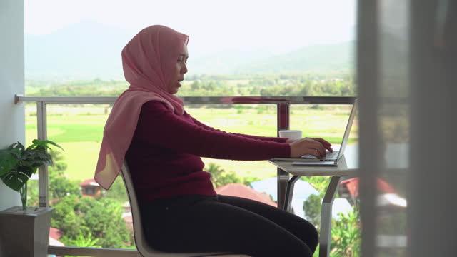 vidéos et rushes de vue latérale: jeunes femmes d'affaires musulmanes en tissu religieux en hiver en utilisant un ordinateur portable et travaillant pendant le travail, présentation hors du bureau sur le balcon d'un hôtel, appartement au milieu de la scène verte, vue  - non urban scene