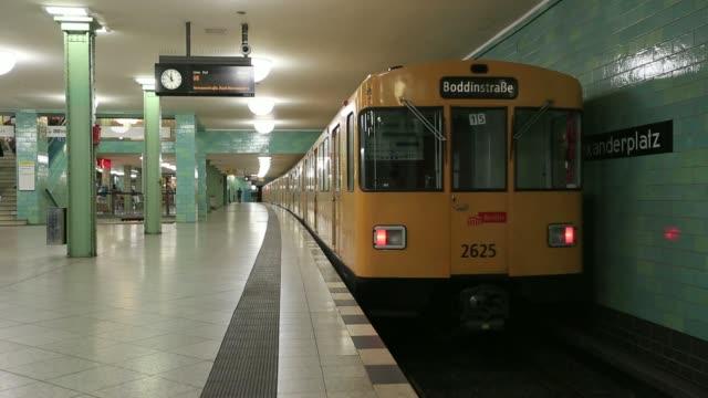 Side views U Bahn Underground trains arrive at and depart a platform at Alexanderplatz station passengers wait on platform and board the trains in...