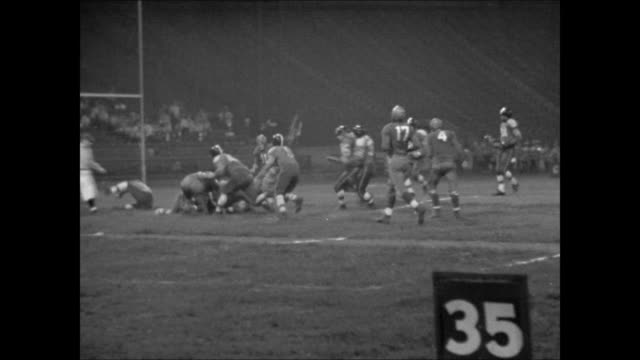 night sideline ws football game in progress player running w/ ball tackled fans in stadium seats standing disappointed ha ws pass play tracking ws... - touch football video stock e b–roll