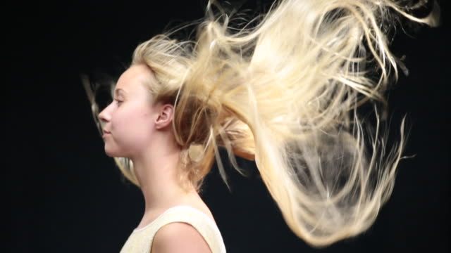 vídeos de stock, filmes e b-roll de ms slo mo sideshot of woman with long blond hair moving in wind / london, greater london, united kingdom - exposto pelo vento