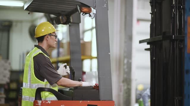 sideview asiatische chinesische Lagerarbeiter betreiben Gabelstapler arbeiten in Industriefabrik