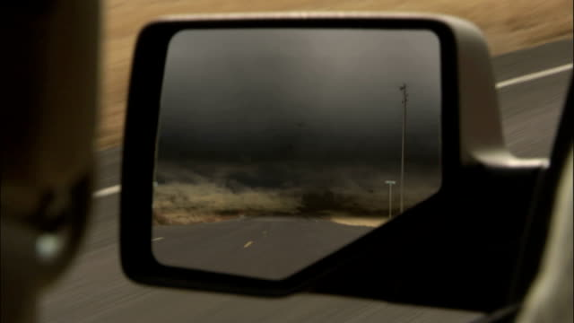 a side-view mirror reflects storm clouds gathering behind vehicle available in hd. - tornado stock videos & royalty-free footage