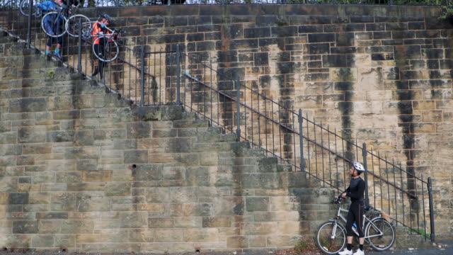 side-view of cyclists down steps - surrounding wall stock videos and b-roll footage