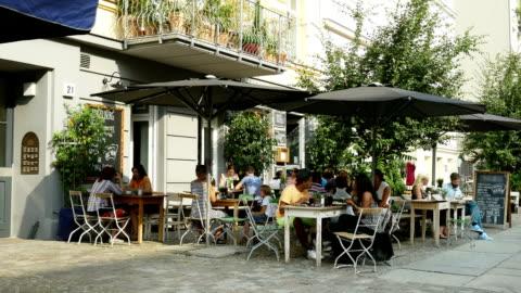 sidewalk cafe in berlin prenzlauer berg (4 k uhd zu/hd) - im freien stock-videos und b-roll-filmmaterial
