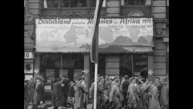 sidewalk w/ people, soldiers walking below sign w/ maps of german colonies in africa pre-wwii. maps on sign of west africa, togo & east africa... - colony stock-videos und b-roll-filmmaterial