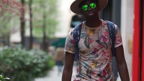 vídeos y material grabado en eventos de stock de sidya sarr wears an asos beige hat, a torino cortese watch, asos necklace and armlace, hawkers green sunglasses, stance socks, nike blazer sneakers... - tartán