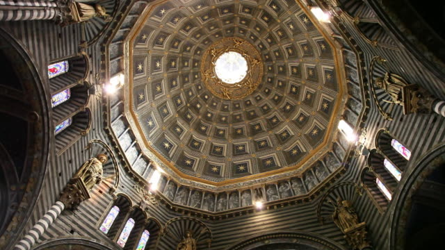 siena cathedral of the most holy mary of assumption (santa maria assunta duomo di siena), dome, gilded lantern, coffers, golden stars, golden statues at the dome's drum, stained-glass lancet windows, siena, italy - dome stock videos & royalty-free footage