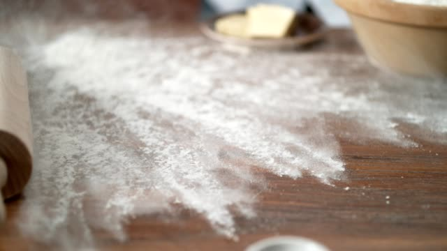 sifting flour onto cutting board. preparing cake batter. super slow motion - lanciare video stock e b–roll