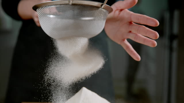 slo mo cu sifting the flour - flour stock videos & royalty-free footage