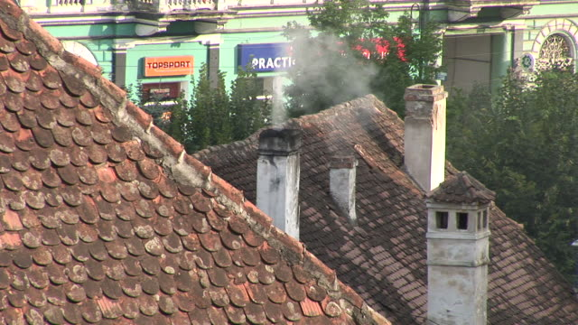 sighisoarasmoke coming out of a chimney sighisoara transylvania romania - トランシルバニア点の映像素材/bロール