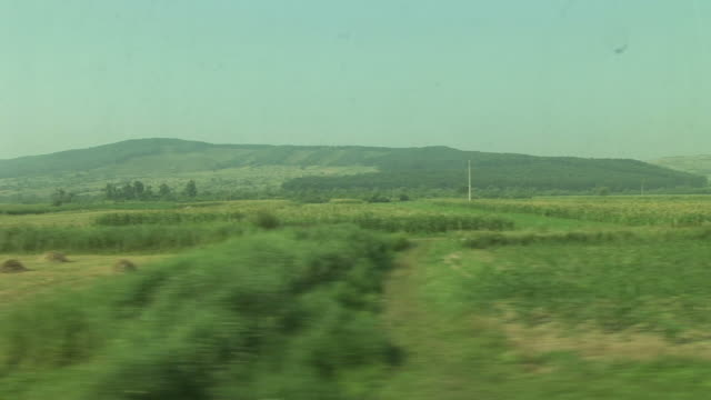 SighisoaraView of agriculture landscape from a moving train in Sighisoara Transylvania Romania