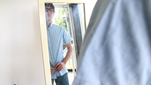 A sight that a man changes clothes while holding a button in front of a mirror.