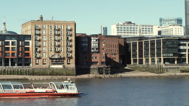 vídeos de stock, filmes e b-roll de ws pan sightseeing boat on river thames at low tide / london, united kingdom - vazante