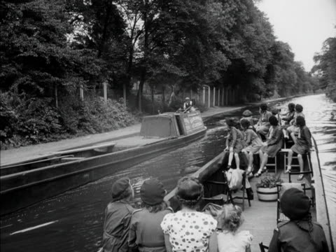 a sightseeing narrow boat passes a barge travelling in the opposite direction on london's grand union canal 1951 - narrow stock videos & royalty-free footage