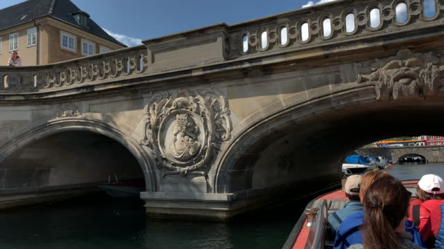 a sightseeing tour tracks beneath one of the many beautiful, ornate bridges crossing the canals of, copenhagen - regione dell'oresund video stock e b–roll