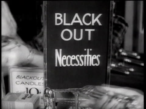 sign advertising blackout necessities, with shoppers' hands moving about it / new york city, new york, united states - 1942 video stock e b–roll