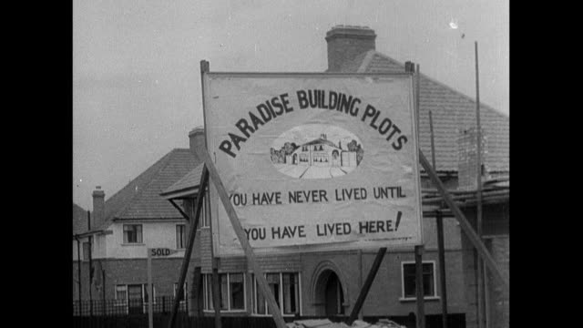 montage sign advertising new home construction, workmen putting finishing touch on front lawn, neighbors meeting by streetlight, homeowner shoving kitten outside, and cat and dog meeting at streetlight / england, united kingdom - 1934 個影片檔及 b 捲影像