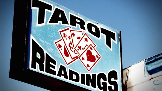 a sign advertising tarot readings towers over a psychic's storefront. - information medium stock videos & royalty-free footage