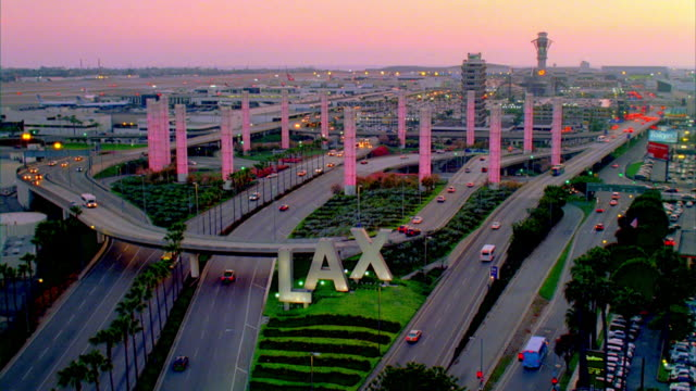 ws lax sign and traffic on elevated road with illuminated towers at dusk / los angeles, california, usa - lax airport stock videos & royalty-free footage