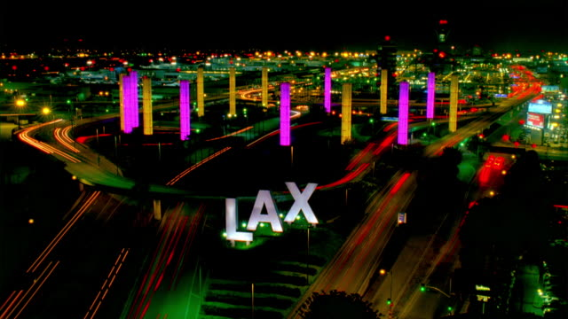 ws t/l lax sign and traffic on elevated road with illuminated towers at night / los angeles, california, usa - lax airport stock videos & royalty-free footage