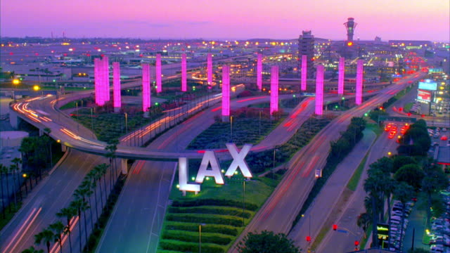 WS T/L LAX sign and traffic on elevated road with illuminated towers at night / Los Angeles, California, USA