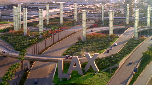 ws lax sign and traffic on elevated road with towers / los angeles, california, usa - lax airport stock videos & royalty-free footage