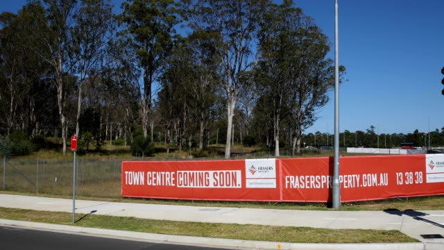 A sign announcing a new town centre coming soon is seen in front of an area of natural bush land set aside for development next to the newly...